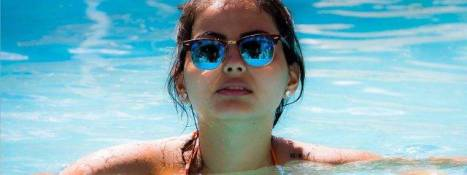 female in pool with sunglasses